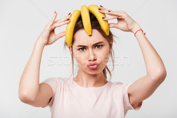 Portrait of a crazy young girl holding bananas Stock photo © deandrobot