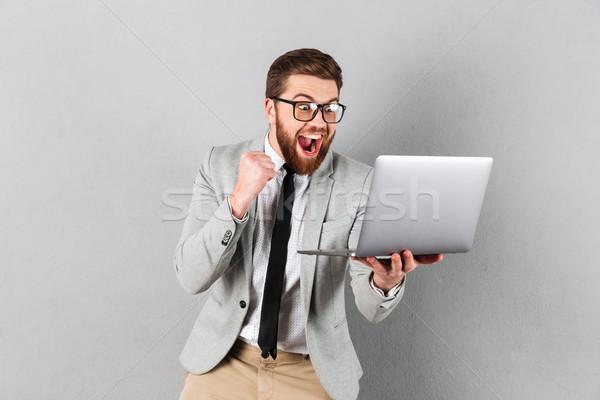 Portré elégedett üzletember öltöny szemüveg tart Stock fotó © deandrobot