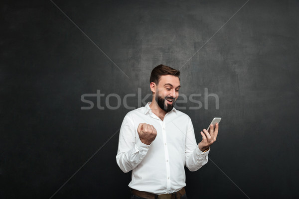 Delighted businessman in white shirt acting like winner clenchin Stock photo © deandrobot