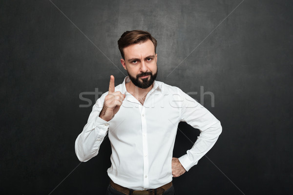 Portrait of serious man 30s in white shirt posing on camera with Stock photo © deandrobot