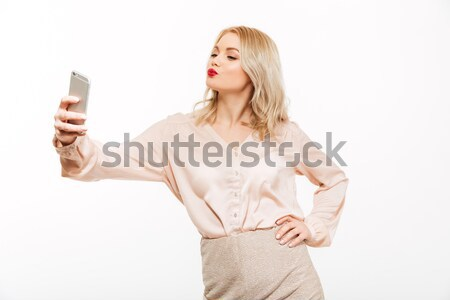 Cute young lady showing display of mobile phone Stock photo © deandrobot