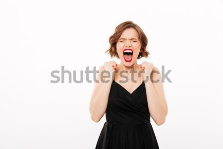 Portrait of an angry girl dressed in black dress screaming Stock photo © deandrobot