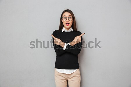 Happy asian woman in business clothes with arm on hip Stock photo © deandrobot