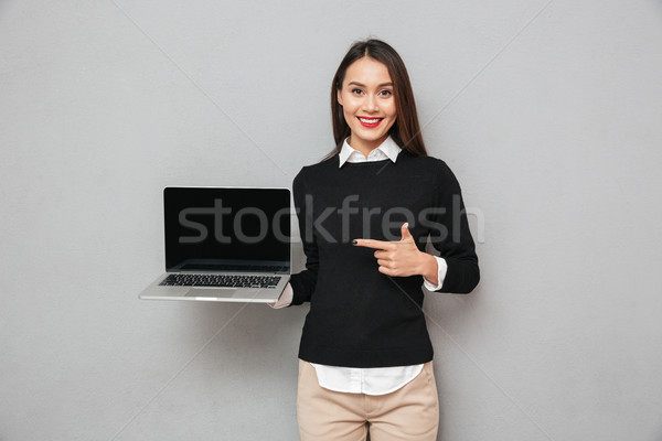 Pleased woman in business clothes showing blank laptop computer screen Stock photo © deandrobot