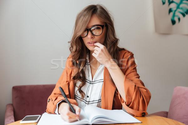 Portrait of a pensive woman taking notes Stock photo © deandrobot