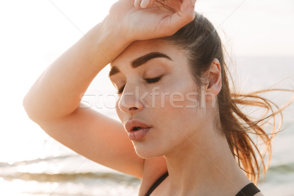 Close up portrait of an exhausted young sportswoman Stock photo © deandrobot