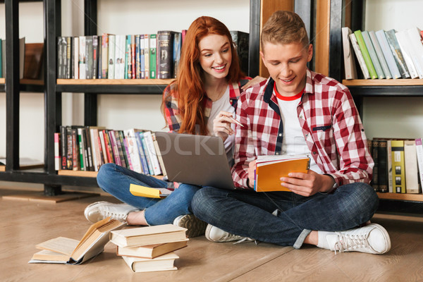 Smart teenage couple sitting on a floor at the bookshelf Stock photo © deandrobot