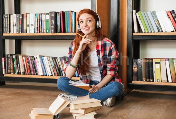 Compiti per casa seduta biblioteca ascoltare musica cuffie Foto d'archivio © deandrobot