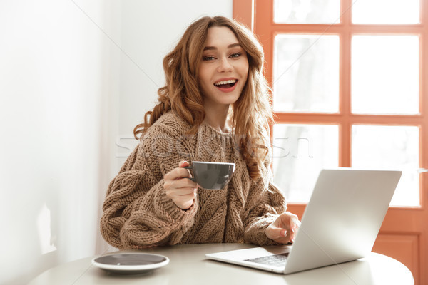 Photo of brunette woman 20s in sweater with long brown hair drin Stock photo © deandrobot