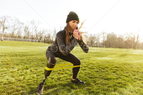 Photo of concentrated disabled girl in tracksuit, doing sports a Stock photo © deandrobot