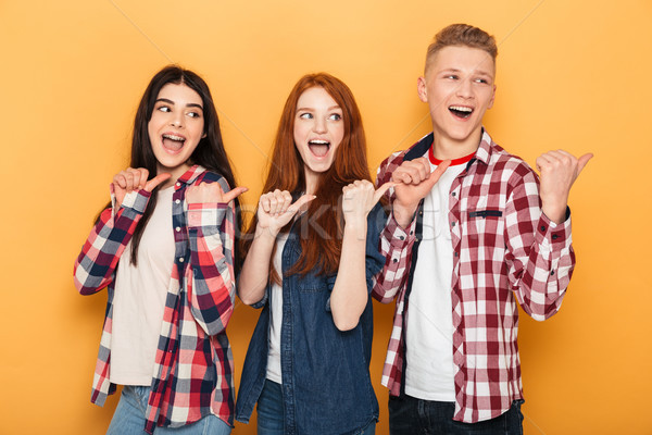 Group of happy school friends pointing fingers away Stock photo © deandrobot