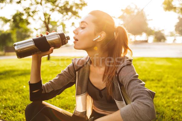 Fotó fiatal fitnessz nő 20-as évek sportruha ivóvíz Stock fotó © deandrobot
