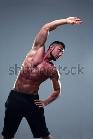 Fiatalember nyújtás kezek rózsaszín meztelen férfi Stock fotó © deandrobot