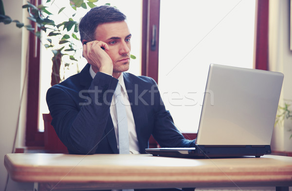 Businessman talking on the phone and using laptop in office Stock photo © deandrobot
