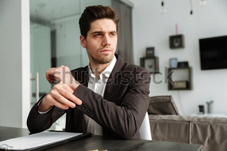 Confident businessman using laptop and talking on the phone at office Stock photo © deandrobot
