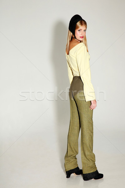 Side view portrait of a young trendy woman on gray background Stock photo © deandrobot