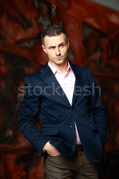 cool trendy man standing over industrial background Stock photo © deandrobot