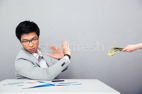 Businessman gesturing stop sign while someone proposing money to him Stock photo © deandrobot