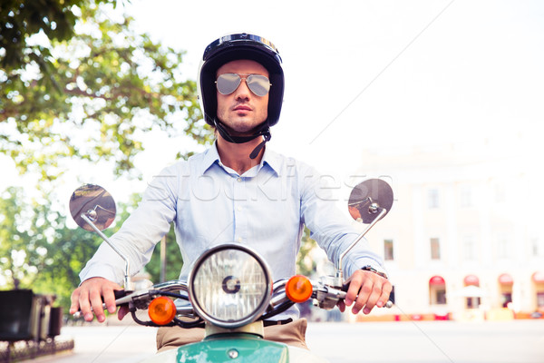Man in helmet riding on scooter  Stock photo © deandrobot