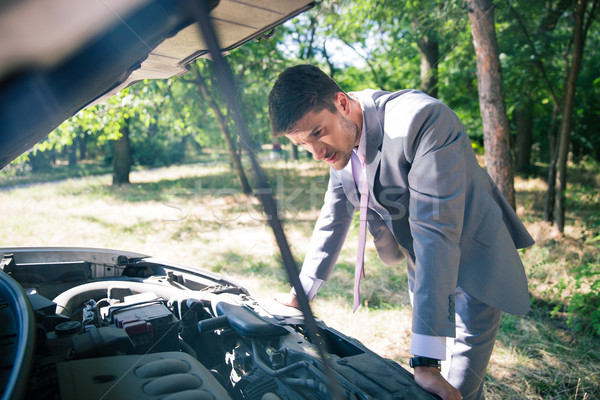 Man looking under the hood of car Stock photo © deandrobot