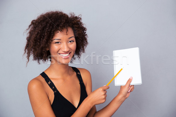 Afro american woman showing blank notebook  Stock photo © deandrobot