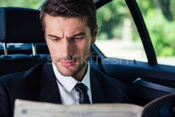 Businessman reading newspaper while riding in car Stock photo © deandrobot