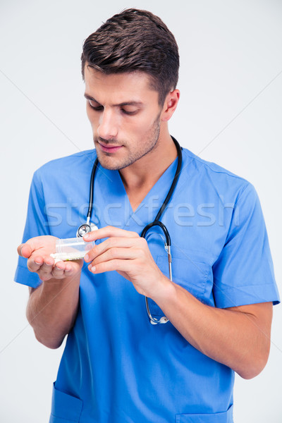 Handsome male doctor standing with tablets  Stock photo © deandrobot