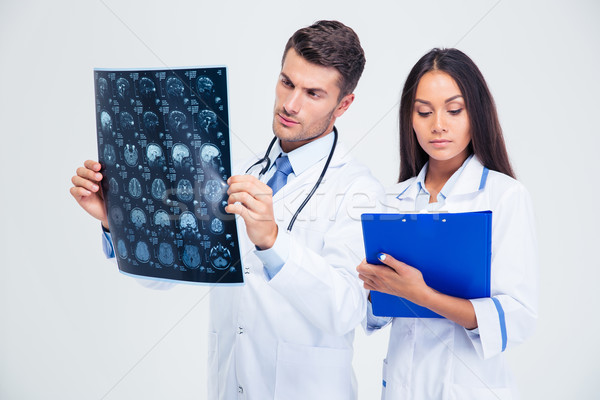 Male doctor looking at x-ray picture of brain Stock photo © deandrobot