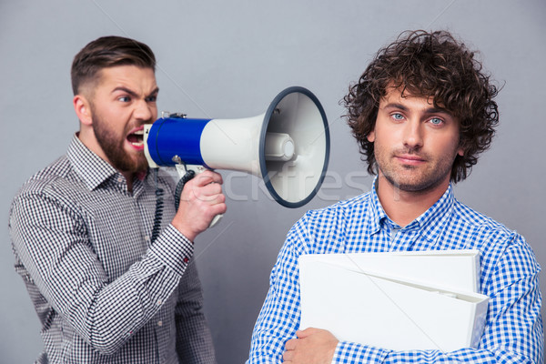 Businessman yelling via megaphone to another man Stock photo © deandrobot