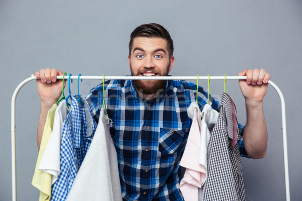 Happy hipster man standing with rack of clothes Stock photo © deandrobot