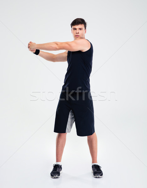 Full length portrait of a fitness man stretching hands Stock photo © deandrobot