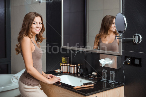 Stock photo: Positive girl staying in bathroom and smiling
