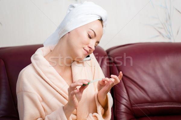 Nyugodt nő fürdőköpeny körmök beszél mobiltelefon Stock fotó © deandrobot