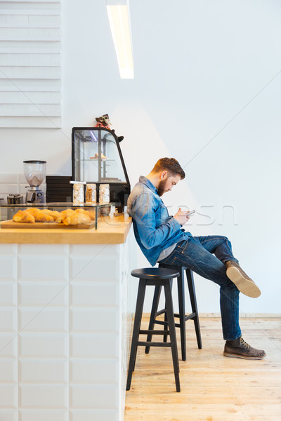 Stock photo: Man using smartphone in cafe
