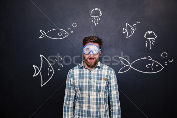 Amazed man in diving mask with open mouth over blackboard  Stock photo © deandrobot