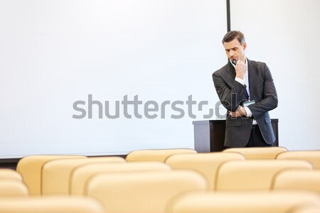 Concentrated speaker repeating speech with tablet in empty boardroom Stock photo © deandrobot