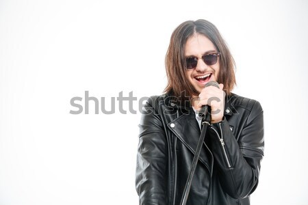 Handsome young rock singer in sunglasses singing into microphone Stock photo © deandrobot