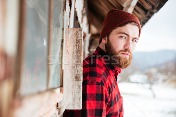 Serious man in old wooden house at village Stock photo © deandrobot