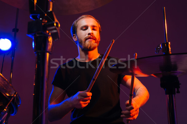 Concentrated bearded musician playing drums with sticks Stock photo © deandrobot