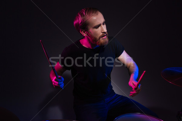Handsome bearded man drummer sitting and playing drums with drumsticks Stock photo © deandrobot