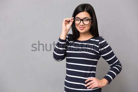 Cheerful girl in glasses showing thumbs up with both hands Stock photo © deandrobot