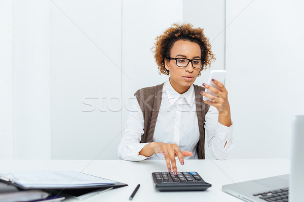 Thoughtful african woman accountant working with calculator and using smartphone Stock photo © deandrobot
