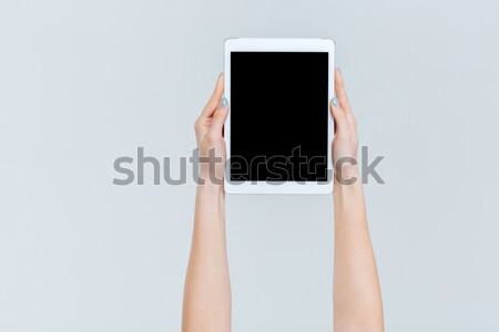 Female hands holding tablet computer with blank screen Stock photo © deandrobot