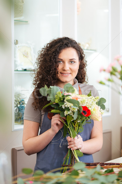 Smiling woman florist enjoying working in flower shop  Stock photo © deandrobot