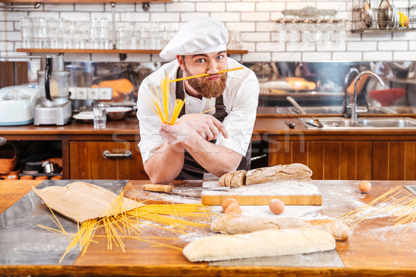 Funny baker making moustache using macarons on the kitchen Stock photo © deandrobot