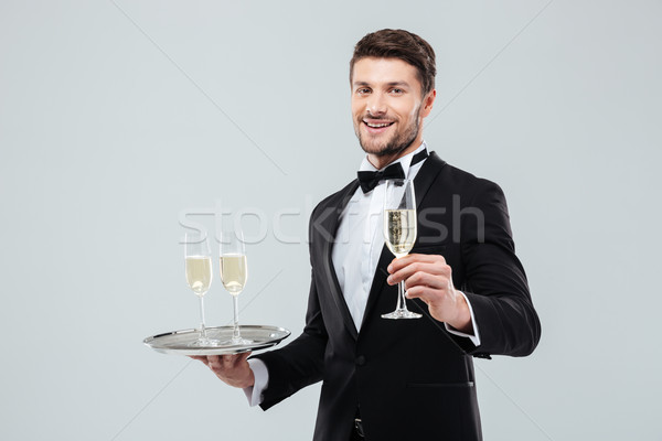 Stock photo: Happy butler in tuxedo holding tray and glass of champagne