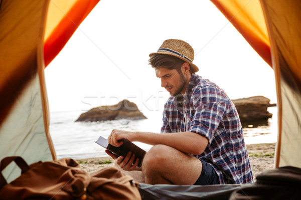 Smiling young man sitting near touristic tent and reading book Stock photo © deandrobot