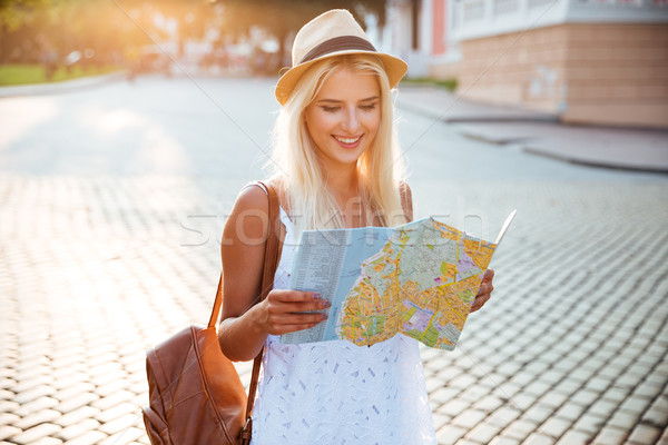 Happy tourist woman on vacation with map visiting city Stock photo © deandrobot