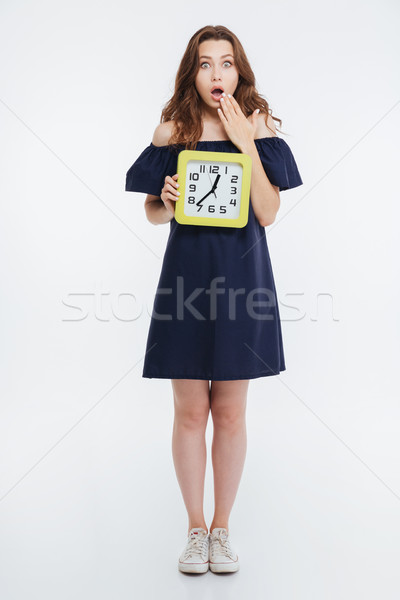 Amazed pretty young woman standing and holding clock Stock photo © deandrobot