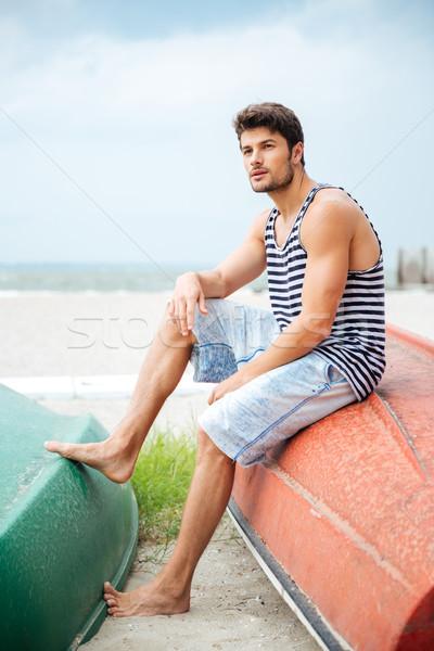 Knap jonge man vergadering vissersboot zee Stockfoto © deandrobot
